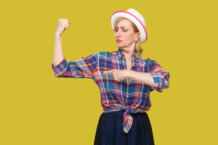 Strong and independent alone. Portrait of proud modern stylish mature woman in casual style with white hat standing and pointing finger at her biceps. indoor studio shot isolated on yellow background.