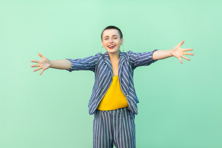 Portrait of happy handsome beautiful short hair young stylish woman in casual striped suit standing with raised arms, want to hug and looking at camera. studio shot isolated on light green background.