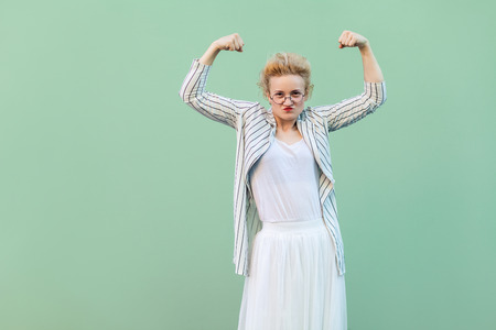independence woman. Portrait of strong proud young blonde woman in white striped blouse with eyeglasses standing with raised arms and looking at camera. studio shot isolated on light green background