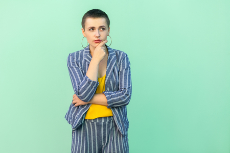 Portrait of thoughtful handsome beautiful short hair young stylish woman in casual striped suit standing with hand on chin and thinking about. indoor studio shot isolated on light green background.