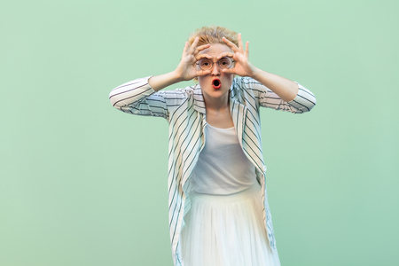 Portrait of surprised young blonde woman in white shirt, skirt, and striped blouse with eyeglasses standing with binoculars hands on eyes. indoor studio shot isolated on light green background.