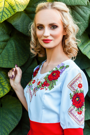 Closeup portrait of attractive blonde woman with makeup, curly hairstyle in stylish red white dress posing on leaves background. looking at camera and smile. outdoor shot in the park at summer daytime Banco de Imagens - 122392177