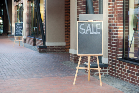 street chalkboard sign display with text sale near shop outdoor. Stock Photo