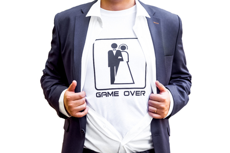 The game is over! newlywed in dark blue costume with opened shirt showing t-shirt with funny picture of marrieds. indoor studio shot isolated on white background.