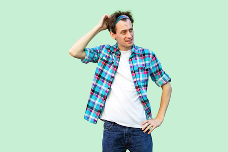 Portrait of thoughtful young man in casual blue checkered shirt and headband standing, scratching his head and thinking what to do. indoor studio shot, isolated on light green background.