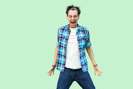 Portrait of angry confused young man in casual blue checkered shirt and headband standing, looking at camera with aggressive face and screaming. indoor studio shot, isolated on light green background. 版權商用圖片