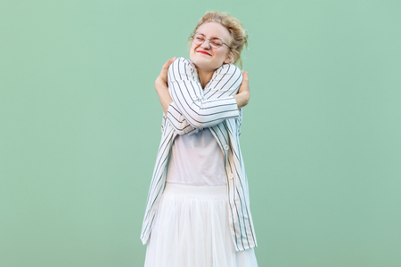 Portrait of happy proud young blonde woman in white shirt, skirt, and striped blouse with eyeglasses standing hugging herself and feeling good. indoor studio shot isolated on light green background. Stock Photo
