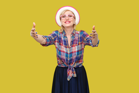 Portrait of happy modern stylish mature woman in casual style with hat and eyeglasses standing giving hands to hug and looking with toothy smile. indoor studio shot isolated on yellow background.