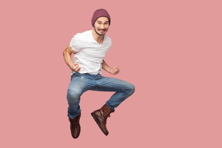 Portrait of happy bearded hipster young man in white shirt and blue jeans with hat jumping, rejoicing and celebrating his victory. indoor studio shot, isolated on pink background copyspace.