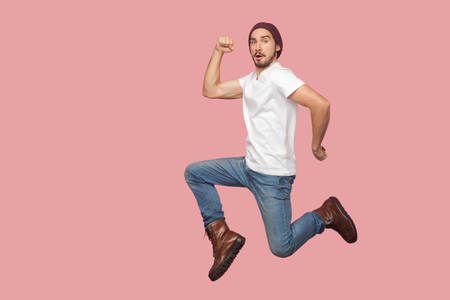 Portrait of carefree bearded hipster young man in white shirt and blue jeans with hat jumping and looking at camera with funny face. indoor studio shot, isolated on pink background