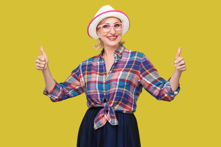 Portrait of happy satisfied modern stylish mature woman in casual style, hat and eyeglasses standing, thumbs up, looking at camera with toothy smile. indoor studio shot isolated on yellow background. Stok Fotoğraf