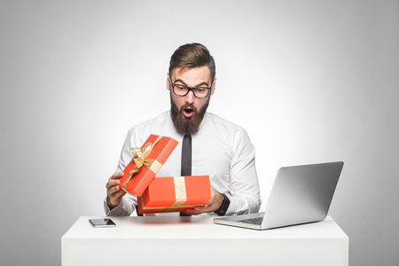 Wow! Suprised young manager in white shirt and black tie are sitting in office and unboxing present with shocked face, big eyes and opened mouth. Indoor, isolated, studio shot, gray background