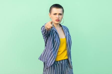 Portrait of serious handsome beautiful short hair young stylish woman in casual striped suit standing looking and blaming at camera. indoor studio shot isolated on light green background.