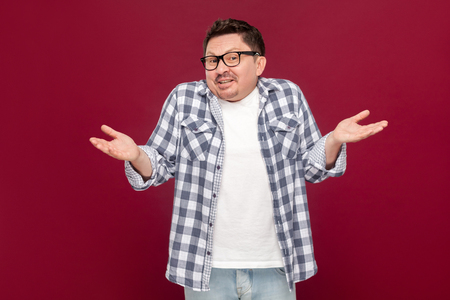 I don't know. Portrait of confused handsome middle aged man in casual checkered shirt and eyeglasses standing with raised arms and dont know what to do. studio shot, isolated on dark red background.