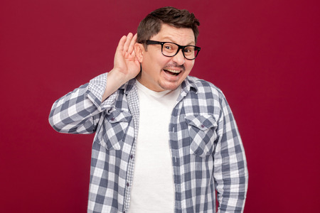 Portrait of funny handsome middle aged business man in casual checkered shirt, eyeglasses standing with hand on ears and looking at camera smiling. indoor studio shot, isolated on dark red background.