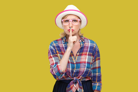 Portrait of serious modern stylish mature woman in casual style with hat and eyeglasses standing with silence sign and asking to be quiet. indoor studio shot isolated on yellow background.