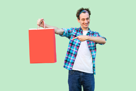Cheerful modern young man in white t-shirt and checkered shirt standing and pointing finger to shopping bags and toothy smile, looking at camera. Studio shot, green background, isolated, indoor