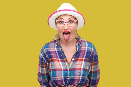 Portrait of funny surprised modern stylish mature woman in casual style with hat and eyeglasses standing tongue out, looking at camera with big eyes. indoor studio shot isolated on yellow background.
