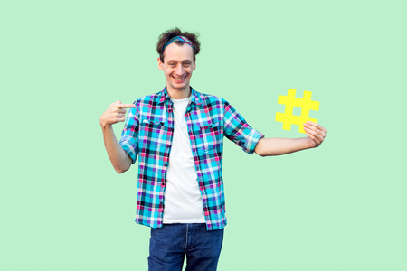 Do you use hashtag? Positive happy young man in checkered shirt holding large big yellow hash tag sign and pointing with finger to it. Indoor, isolated, studio shot, copy space, green background