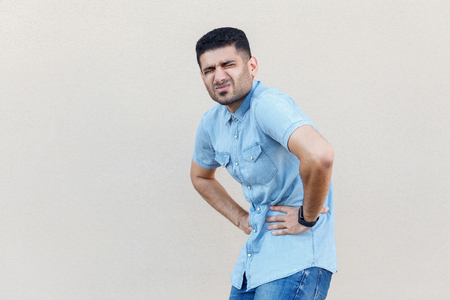 Stomach pain or diet problem. Portrait of sick handsome young bearded man in blue shirt standing and holding his painful belly, feeling bad. indoor studio shot isolated on light beige wall background. Stock Photo