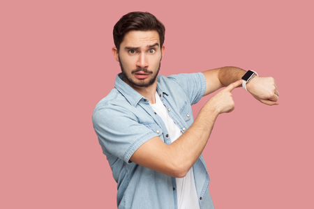 Time is out. Portrait of serious handsome bearded young man in blue casual style shirt standing and looking at camera, pointing on his smart watch. indoor studio shot, isolated on pink background. Standard-Bild