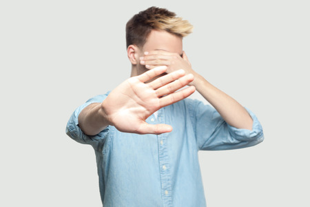 Stop, I don't want to see at this. Portrait of scared handsome young man in light blue shirt standing, covering his face and showing stop hand gesture. indoor studio shot on grey background copy space