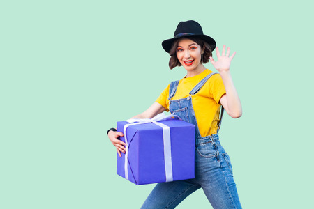Cheerful happy young girl in hipster wear in denim overalls and black hat standing and trying to hold giant big heavy gift box and greeting you, showing five. Studio shot, green background, isolated