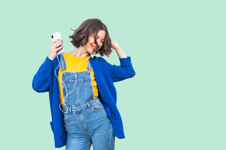 Portrait of beautiful carefree young adult woman in hipster wear in denim overalls standing, holding phone and listening her favourite music with handsets and dancing. Studio shot, green background