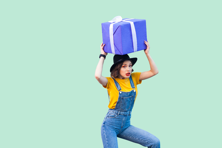 Suprised funny young girl in hipster wear in denim overalls and black hat standing and holding under head giant big heavy gift box with unbelievable face. Studio shot, green background, isolated