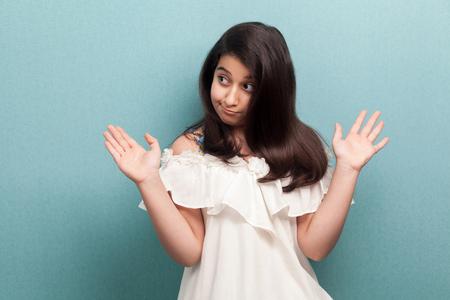 Je ne sais pas. Portrait d'une belle jeune fille confuse aux cheveux longs et raides noirs en robe blanche debout, les bras levés, les épaules et la pensée. tourné en studio intérieur isolé sur fond bleu