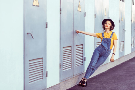young woman in blue denim overalls and yellow tshirt with black hat sensual looking at camera while posing near industrial building . outdoor shot in the summertime