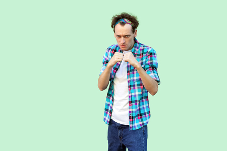 Portrait of angry young man in casual blue checkered shirt and headband standing and looking at camera with boxing fists and ready to attack. indoor studio shot, isolated on light green background. Фото со стока