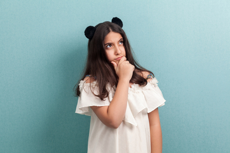 Portrait of thoughtful beautiful brunette young girl with black long straight hair in white dress standing, touching her chin, looking away and thinking. indoor studio shot isolated on blue background