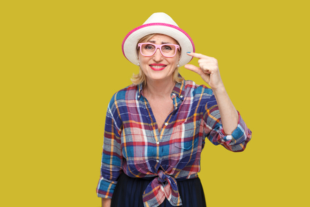 I need a little more. Portrait of pleased modern stylish mature woman in casual style with hat and eyeglasses standing and asking for something more. indoor studio shot isolated on yellow background.