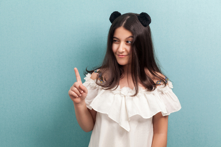 Portrait of funny beautiful brunette young girl with black long straight hair in white dress standing, looking away with finger up, idea or warning. indoor studio shot isolated on blue background.