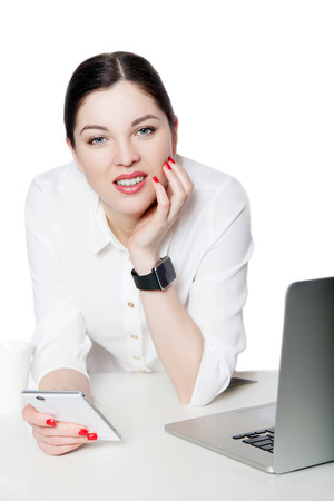 Portrait of happy successful attractive brunette businesswoman in white shirt sitting, holding her smartphone mobile, looking at camera, toothy smile. indoor studio shot, isolated in white background.