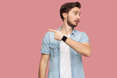 Get out of here. Portrait of angry handsome bearded young man in blue casual style shirt standing and showing out side exit way. indoor studio shot, isolated on pink background.