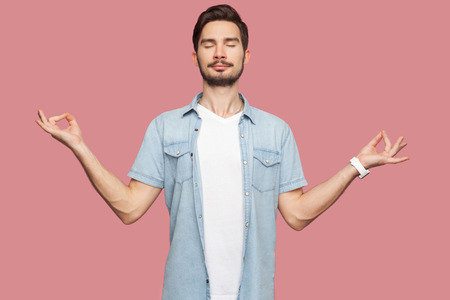 Portrait of calm relaxed handsome bearded young man in blue casual style shirt standing with raised arms and doing yoga meditating exercise. indoor studio shot, isolated on pink background. Stock Photo