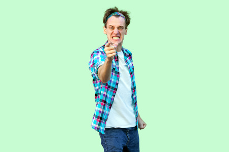 Portrait of angry nervous young man in casual blue checkered shirt and headband standing, clenching teeth, blaming and looking at camera. indoor studio shot, isolated on light green background. Stock Photo