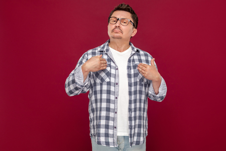Because I am. Portrait of proud satisfied handsome middle aged businessman in casual checkered shirt, eyeglasses, pointing himself, looking at camera. studio shot, isolated on dark red background.