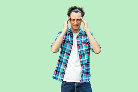 Headache or confuse. Portrait of sad or sick young man in casual blue checkered shirt and headband standing and holding his head and feeling bad. indoor studio shot, isolated on light green background Stock Photo