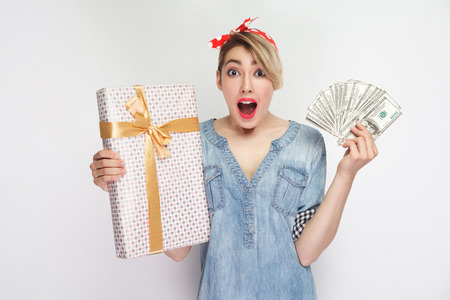 Portrait of amazed young girl in casual denim shirt with makeup and red headband standing, showing gift box and fan dollars with opened mouth. Stock Photo - 123796503