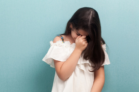 Portrait of sad unhappy beautiful brunette young girl with black long straight hair in white dress standing and crying. indoor studio shot isolated on blue background. Stock Photo
