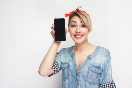 Portrait of funny beautiful young woman in casual blue denim shirt with makeup and red headband standing, holding smartphone near face, looking at camera.Indoor, isolated, studio shot, grey background Stock Photo