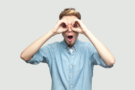 Portrait of shocked handsome young man in light blue shirt standing with hands on eyes binoculars gesture and looking at camera with surprised face. indoor studio shot on grey background copy space. Stock Photo