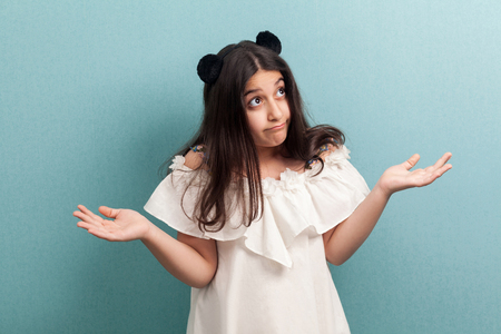 Portrait of confused beautiful young girl with black long straight hair in white dress standing with raised arms shoulders up and thinking. indoor studio shot isolated on blue background