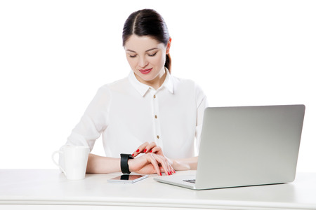 Portrait of happy attractive brunette businesswoman in white shirt sitting looking and touching her smartwatch display, reading something and smiling. indoor studio shot, isolated in white background.