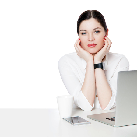 Portrait of calm attractive brunette businesswoman with makeup in white shirt sitting with laptop, touching her face and looking at camera with smile. indoor studio shot, isolated in white background.
