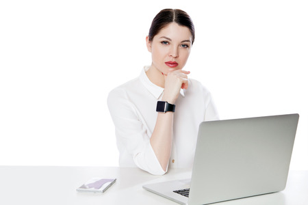 Portrait of serious successful brunette businesswoman in white shirt sitting with laptop, touhing her chin and looking at camera with thoughtful face. indoor studio shot, isolated in white background.
