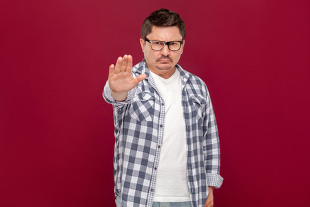 Portrait of serious middle aged business man in casual checkered shirt and eyeglasses standing with stop gesture hand sign and looking at camera.